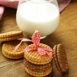 Royalty-Free Stock Photo: Homemade cookies (sandwich) with milk on a wooden table