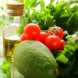 Still life of fresh vegetables (avocado, tomato) olive oil and herbs — Stock Photo #25746403