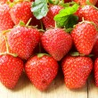 Lots of fresh ripe strawberries on a wooden board — Stock Photo