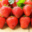 Lots of fresh ripe strawberries on a wooden board — Stock Photo #25839213