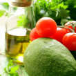 Still life of fresh vegetables (avocado, tomato) olive oil and herbs — Stock Photo #25978025