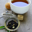 Black tea leaves in a metal strainer on a wooden table — Stock Photo