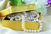 Pearl necklace in a gold gift box — Stock Photo