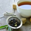 Stock Photo: Black tea leaves in a metal strainer on a wooden table