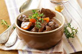 Beef goulash (stew) with vegetables and herbs on a wooden table — Stock Photo