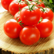 Branch of ripe red tomato on a wooden stump — Stock Photo