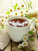 Cup of tea and chamomile flowers on a wooden table — Stock Photo