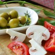 Green olives with vegetables (tomato and mushrooms) on a wooden table — Стоковая фотография
