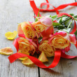 Bouquet of orange roses and red ribbon on a wooden table — Stock Photo