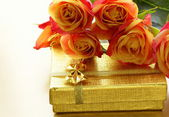 Orange roses and box with gifts on gold background — Stock Photo