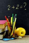 Stationery (pen, pencil, ruler, compass) and a book on black school board background — Stock Photo