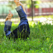 Little child lying on a green lawn, focus on the foreground on the grass — Stock Photo