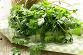 Bunch of fresh green coriander (cilantro) on a wooden table — Stock Photo