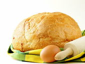 Large loaf of homemade bread with a kitchen towel — Stock Photo