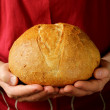 Loaf of homemade bread in the chef hands — Stock Photo