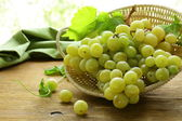Organic white grapes in a basket on a wooden table — Stockfoto