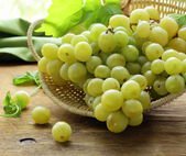 Organic white grapes in a basket on a wooden table — ストック写真