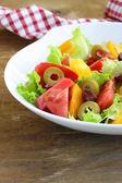 Insalata di pomodori colorati e olive sul tavolo in legno — Foto Stock