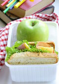 Sandwich with ham, green salad and apple in a box - school lunch — Stock Photo