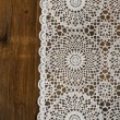 Wooden background with white lace napkin — Stock Photo