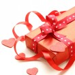 Red gift box with ribbon and hearts on a white background — Stock Photo