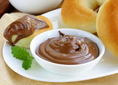 Chocolate nut paste (nutella) for breakfast with bread rolls — Stock Photo