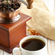 Stockfoto: Wooden coffee grinder and espresso cup on table