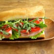 Stock Photo: Baguette sandwich with arugula, ham and tomatoes