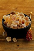 Rock candy sugar in a cup on wooden table — Stockfoto