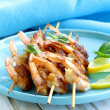 Shrimp grilled on wooden skewers with lemon and basil — Stock Photo