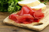Smoked meat bresaola on a cutting board — Stockfoto
