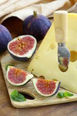 Piece of cheese (Maasdam) with fresh figs on a wooden board — Stock Photo