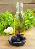 Olive oil flavored with black truffle on a wooden table — Stock Photo