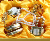 Gold jewelry and pearls in a yellow gift box — Stock Photo