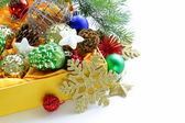 Christmas decorations (balls, cones, stars) in the yellow box — 图库照片