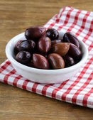 Ripe black kalamata olives in a white bowl — Stock Photo