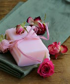 Homemade soap with roses on a wooden table — Stock Photo