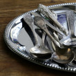 Vintage cutlery with old-fashioned napkin on a silver tray — Stock Photo