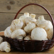Stock Photo: Organic mushrooms (champignons) in basket on wooden background