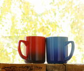 Two colorful coffee mugs in the autumn background — Stock Photo
