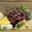 Cheeseboard (Maasdam, Roquefort, Camembert) and grapes for dessert — Stock Photo #32785129