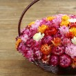 Wicker basket with multicolored flowers on wooden table — Stock Photo