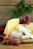Cheeseboard (Maasdam, Roquefort, Camembert) and grapes for dessert — Stock Photo