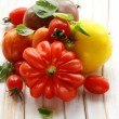 Different varieties of tomato with basil on a wooden table — Stockfoto