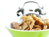 Healthy breakfast - muesli and apple (alarm clock in the background) — Stock Photo