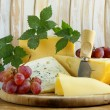 Cheeseboard (Maasdam, Roquefort, Camembert) and grapes for dessert — Stock Photo #33225893