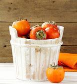 Orange ripe persimmon in a wooden table — Stock Photo