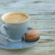 Blue cup of cappuccino on vintage wooden background — Stock Photo
