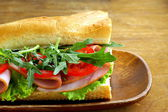 Baguette sandwich with arugula, ham and tomatoes — Stock Photo