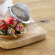 Herbal tea from the dried flower buds of roses in a wooden spoon — Stock Photo